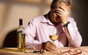 Мужчина держит рюмку с вином