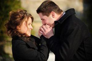 Мужчина целует руки женщине