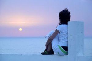 Девушка смотрит на закат солнца