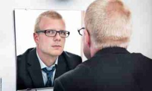 мужчина смотрит на себя в зеркало