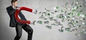 мужчина притягивает магнитом долларовые купюры