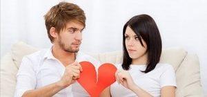 молодые люди разрывают бумажное сердце пополам