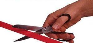 человек при помощи ножниц перерезает красную ленту