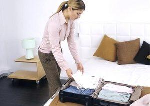 девушка кладет вещи в чемодан