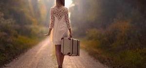 девушка с чемоданом идет по тропинке