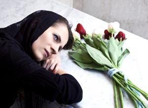 женщина склонилась над могилой