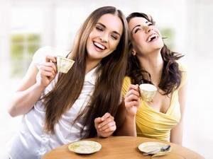 девушки смеются за чашечкой кофе