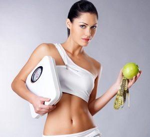 девушка держит в руках весы, сантиметр и яблоко